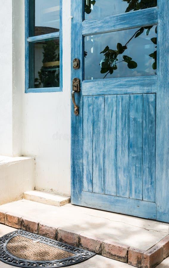 Porta de madeira azul com capacho velho foto de stock royalty free