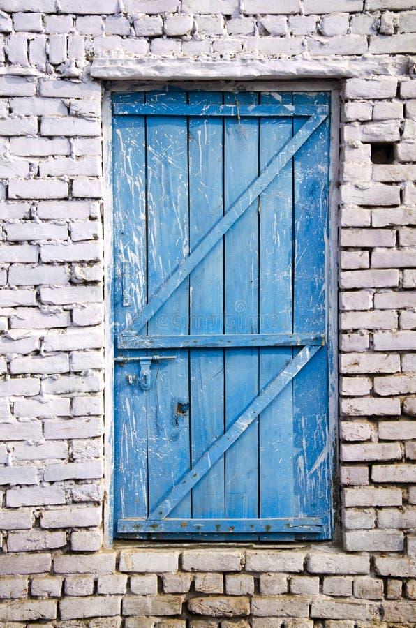 Porta de madeira azul na parede de tijolo branca imagens de stock royalty free