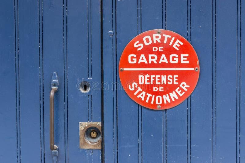 A porta de madeira azul sem o estacionamento canta em francês foto de stock