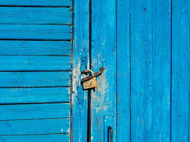 A porta de madeira com descascamento da pintura azul é travada com um cadeado imagens de stock royalty free