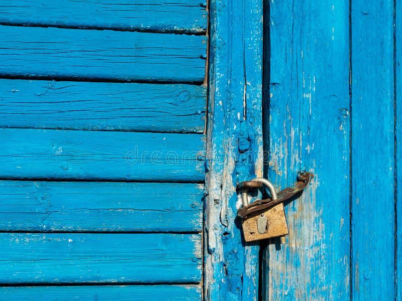A porta de madeira com descascamento da pintura azul é travada com um cadeado imagem de stock
