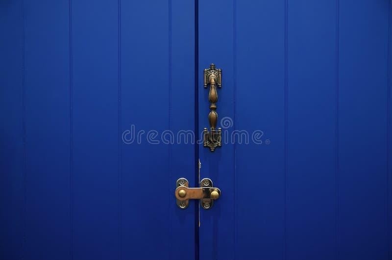 Porta de madeira com punho do metal e fechado azuis: Close up fotos de stock