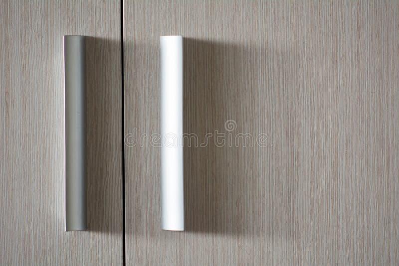 Porta de madeira da textura do fundo com os punhos metálicos plásticos foto de stock