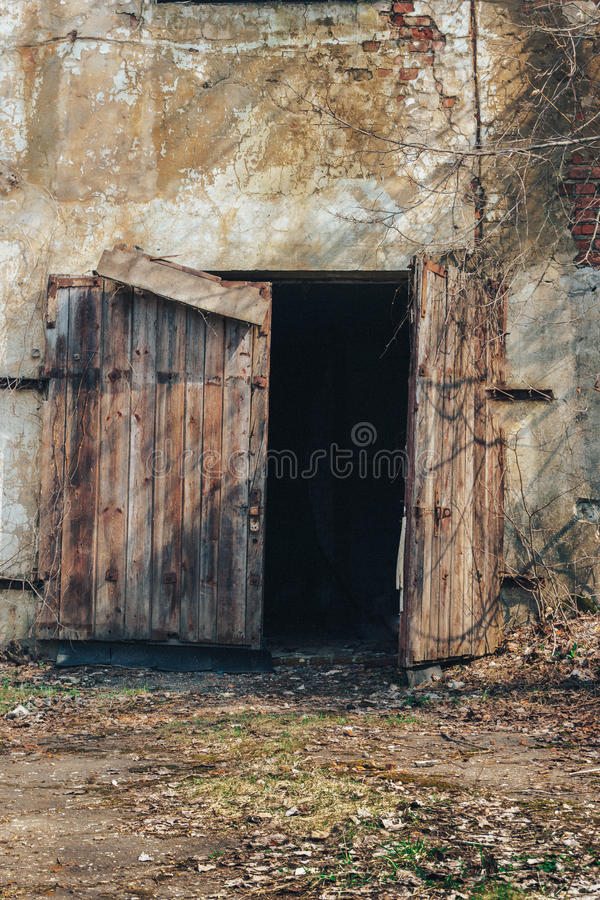 A porta de madeira desmoronou no armazém abandonado velho da fábrica fotos de stock royalty free