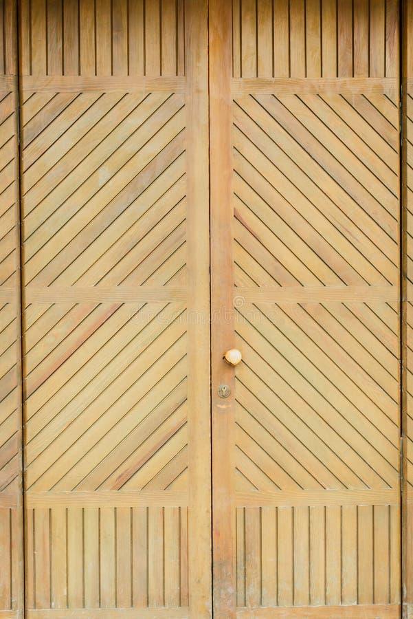 Porta de madeira do vintage com obturadores em uma parede de tijolo vermelho imagem de stock