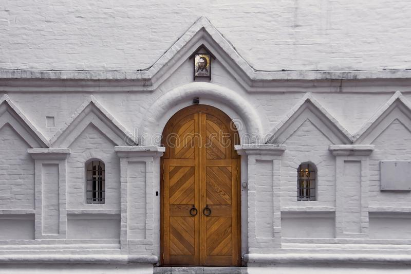 Porta de madeira e duas janelas arqueadas em uma parede de tijolo branca Entrada à igreja cristã velha imagens de stock royalty free