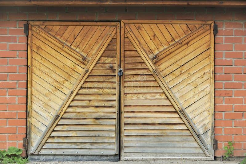 Porta de madeira e paredes de cimento rachadas com alvenaria de tijolos vermelhos Face de um pequeno edifício agrícola com grama  imagens de stock royalty free