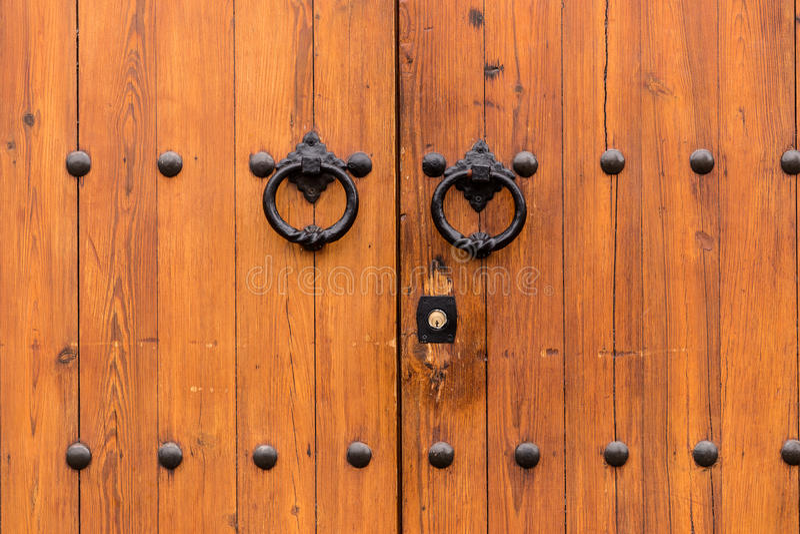 Porta de madeira fechado antiga com dois anéis da aldrava de porta fotografia de stock