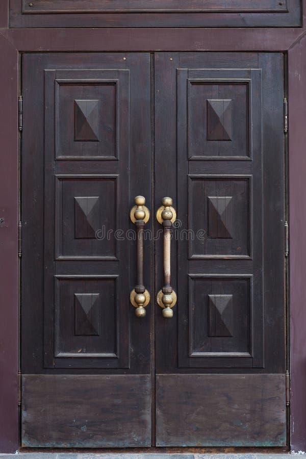 Porta de madeira fechado com punhos do ouro fotografia de stock