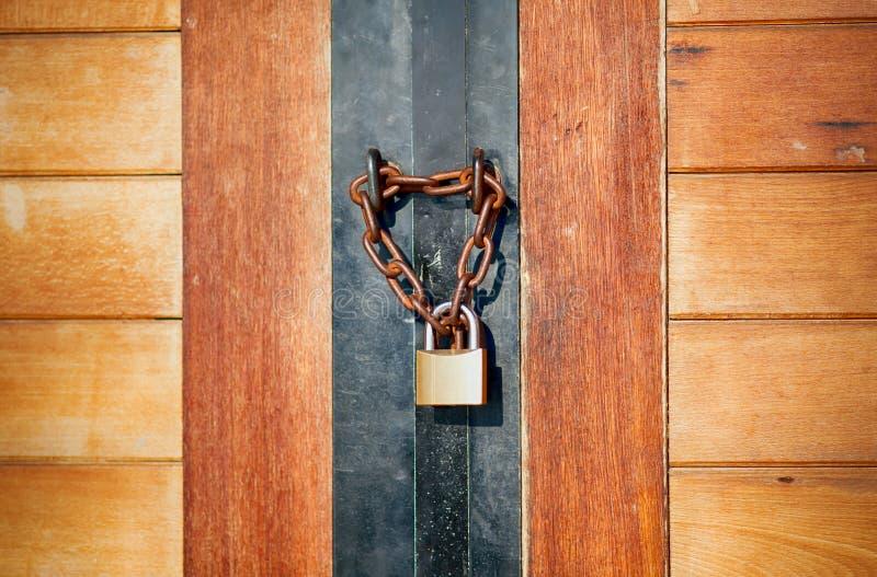 Porta de madeira fechado pela corrente e pelo cadeado imagem de stock