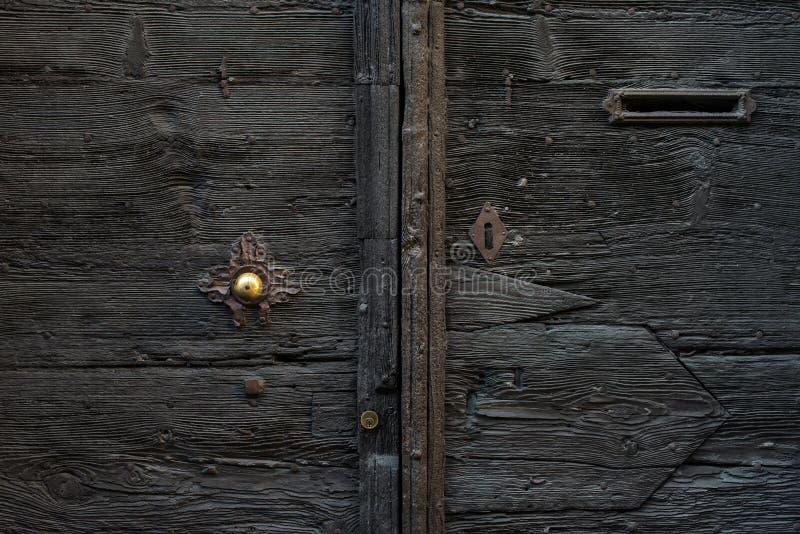 Porta de madeira italiana medieval velha com punho do metal e um entalhe de correio imagens de stock royalty free