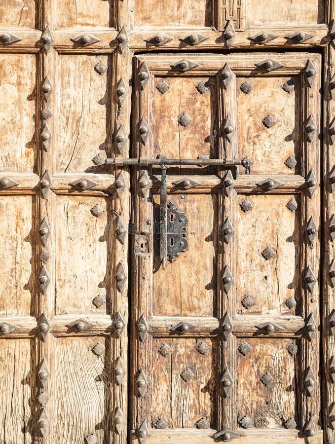 Porta de madeira marrom antiga com ornamento metálicos e um parafuso grande fotografia de stock royalty free