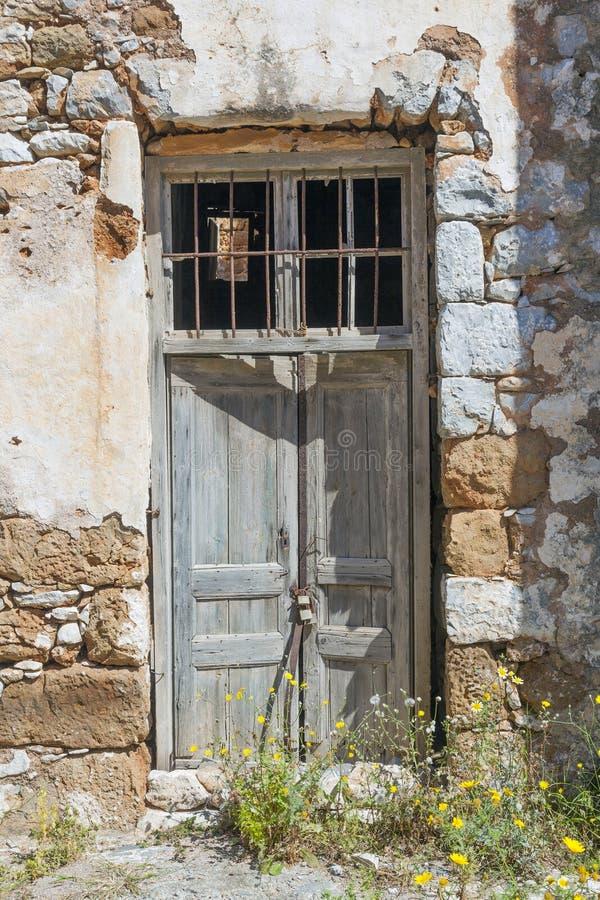 Porta de madeira muito velha com o cadeado na parede de pedra antiga do grego foto de stock