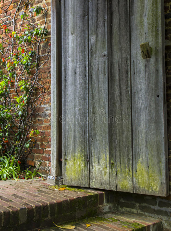 A porta de madeira velha abre a um jardim esquecido imagens de stock