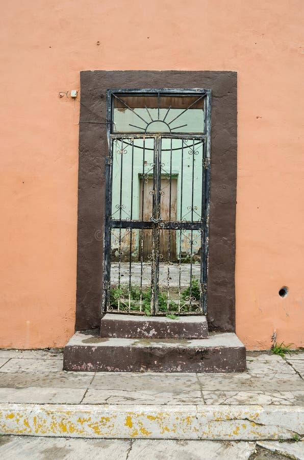 Porta de madeira velha com barras oxidadas em uma parede velha e quebrada fundo para textos, espaço para textos imagem de stock royalty free
