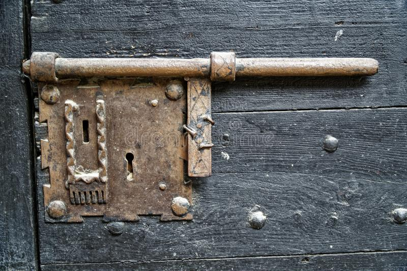 Porta de madeira velha com botão do metal e parafuso medieval oxidado fotografia de stock