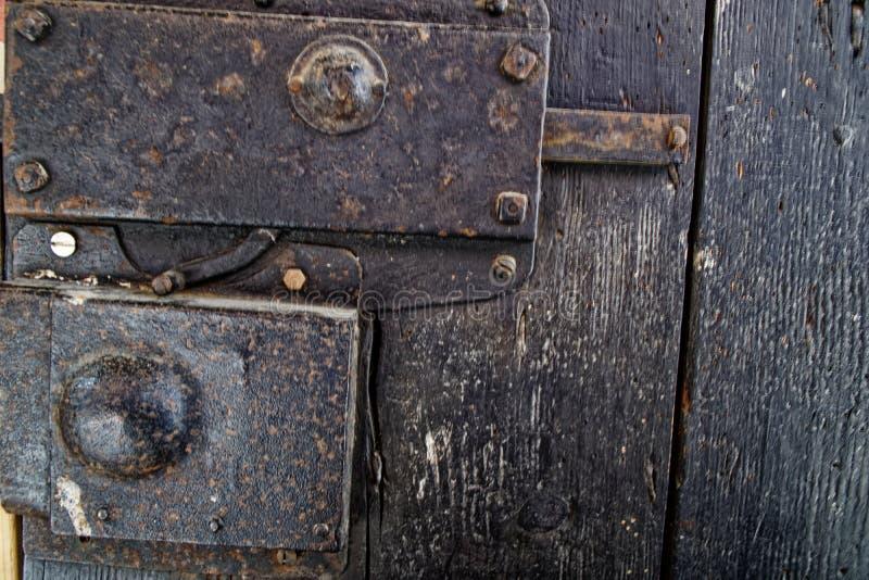 Porta de madeira velha com botão do metal e parafuso medieval oxidado foto de stock royalty free