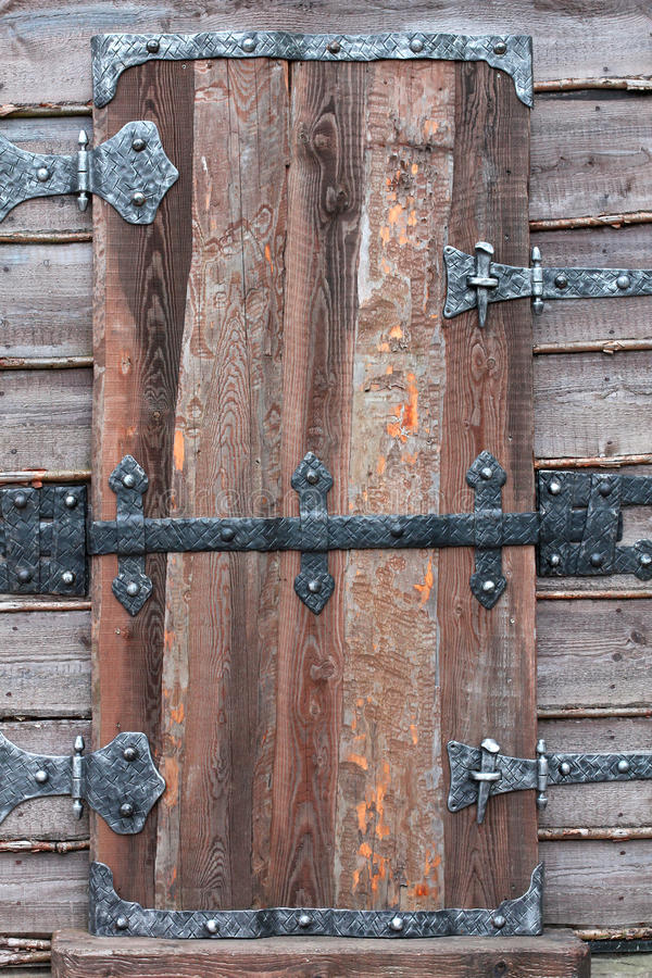 Porta de madeira velha com dobradiças e fechamento do metal imagem de stock royalty free