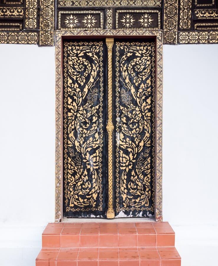 Porta de madeira velha com o teste padrão tailandês tradicional fotografia de stock royalty free