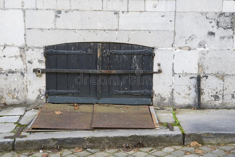 Porta de madeira velha com obturadores, placa do ferro, na parede Maastricht, os Países Baixos fotos de stock royalty free