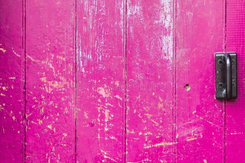 A porta de madeira velha cor-de-rosa scarred com punho preto imagens de stock