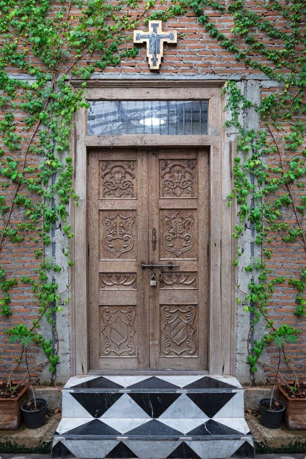 Porta de madeira velha da igreja no jardim fotografia de stock royalty free