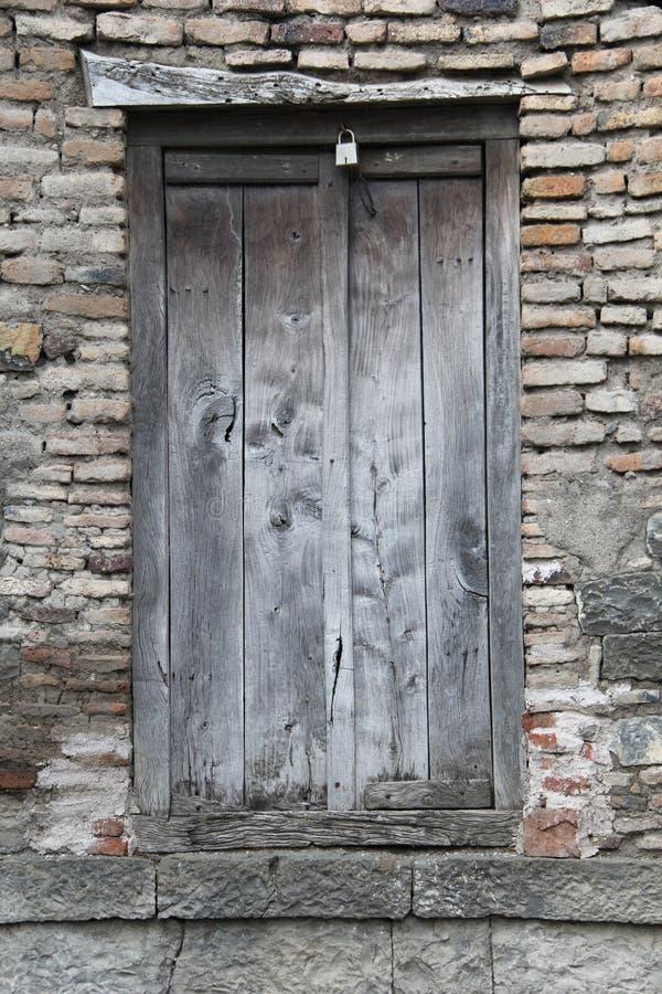 Porta de madeira velha na parede de pedra do tijolo fotografia de stock royalty free