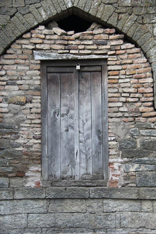 Porta de madeira velha na parede de pedra do tijolo imagens de stock