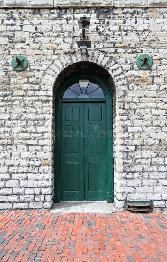 Porta de madeira verde na construção de pedra branca fotografia de stock royalty free
