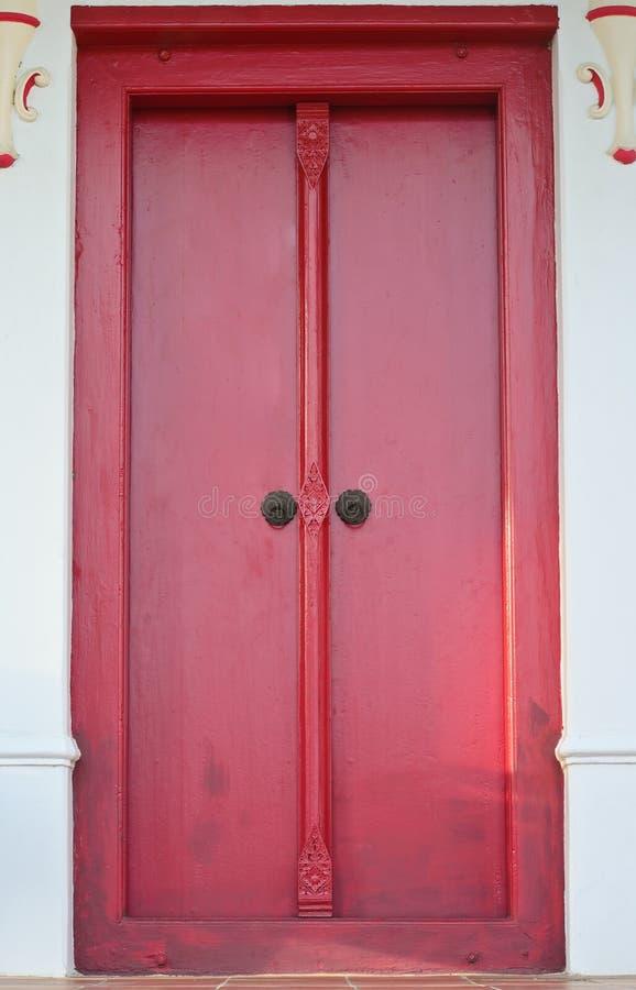 Porta de madeira vermelha tailandesa com cinzeladura tradicional fotos de stock royalty free