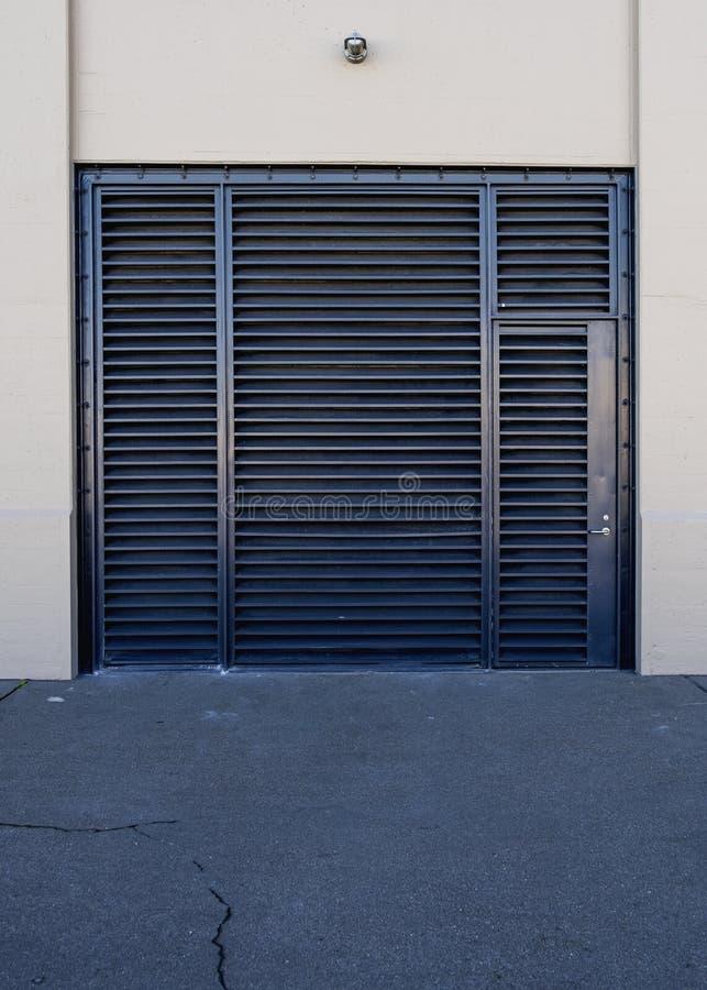 Porta de segurança de metal preto num edifício bege com uma calçada rachada à frente fotos de stock royalty free