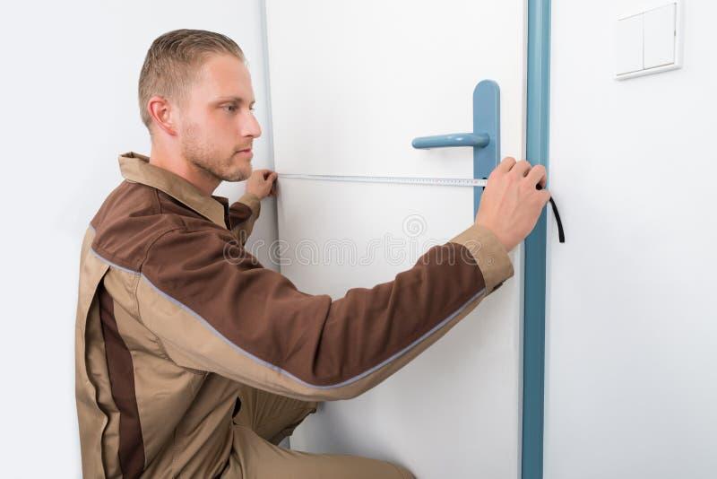 Porta de Taking Measurement Of do carpinteiro fotografia de stock royalty free