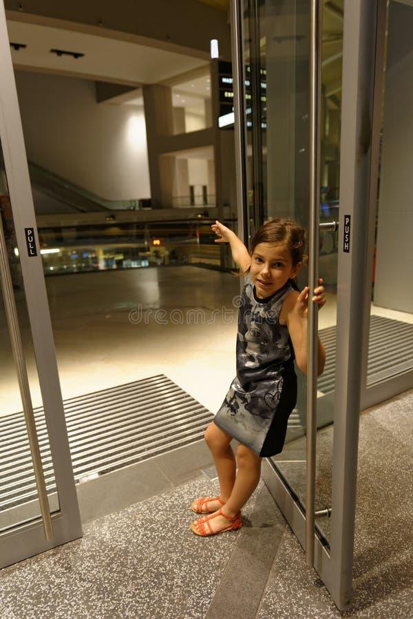 Porta de vidro aberta da terra arrendada da menina fotos de stock