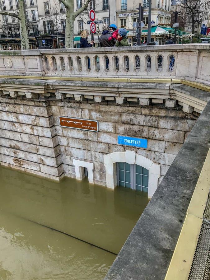 Porta della toilette pubblica sotto le acque di inondazione sulle banche della Senna, Parigi, Francia immagini stock