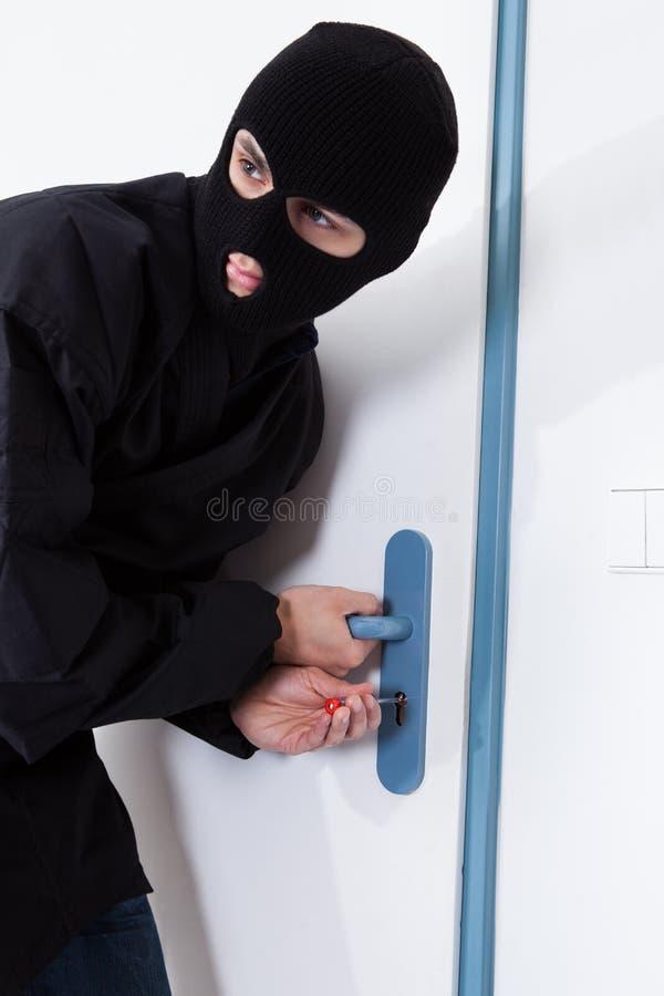 Porta di apertura del ladro con lo strumento durante la pausa della casa immagine stock libera da diritti