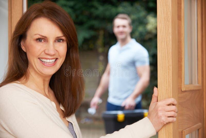 Porta di apertura della donna per riparare uomo immagine stock