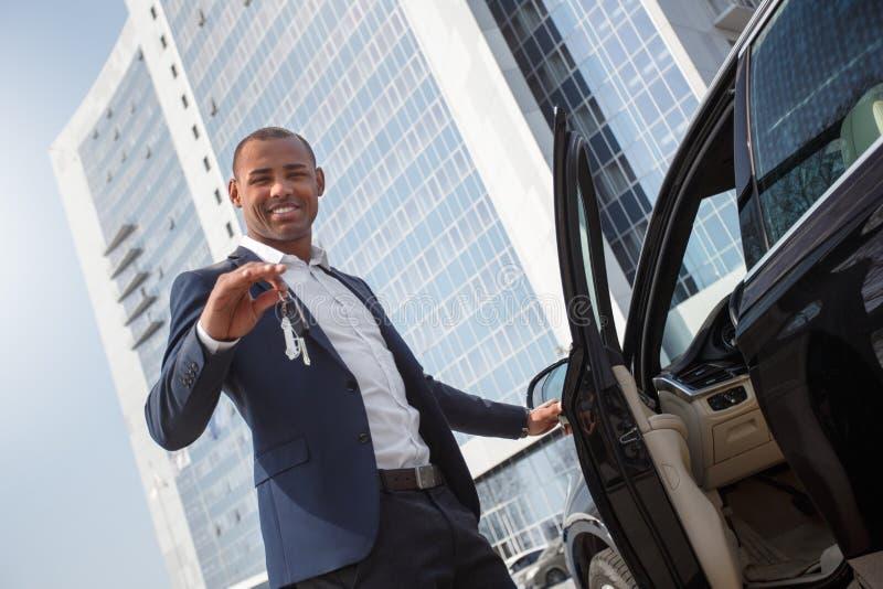Porta di automobile d'apertura di condizione del giovane che tiene le chiavi che guardano vista dal basso allegra della macchina  immagine stock libera da diritti