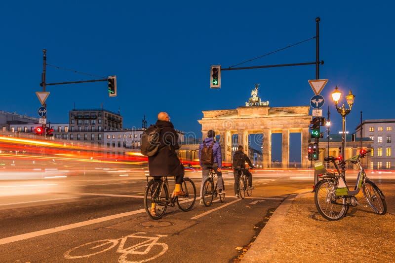Porta di Brandeburgo alla notte con i ciclisti ai semafori immagini stock libere da diritti