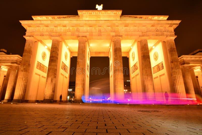 Porta di Brandeburgo di Berlino di notte con una serie di colori provenienti dal veicolo di passaggio che mostra il contrasto tra immagini stock