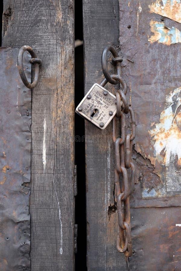 Porta di legno antica con la serratura e la catena del ferro fotografia stock