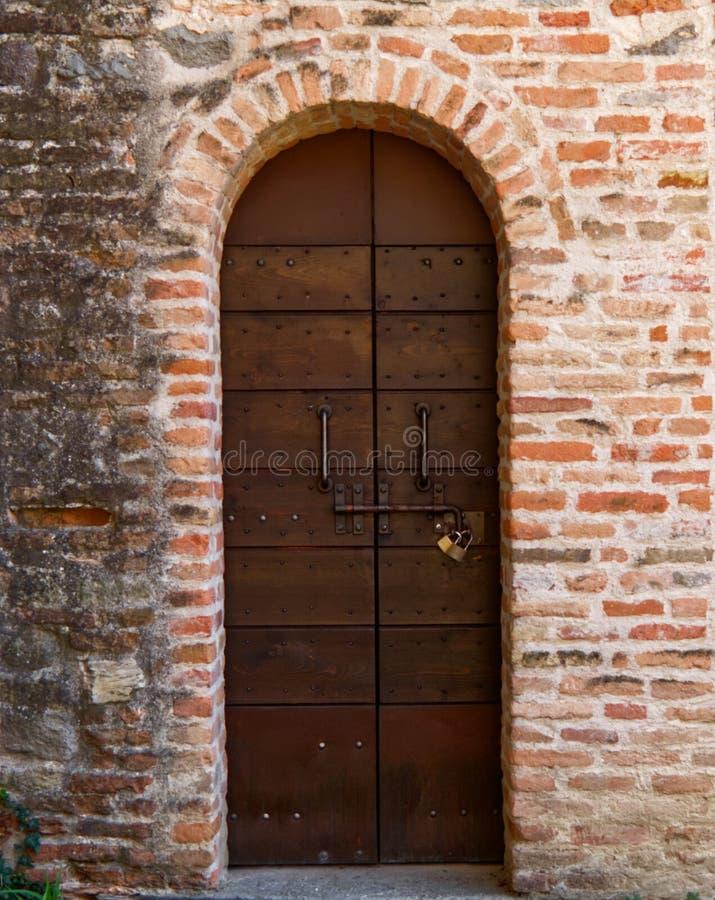 Porta di legno antica e portone di pietra in Italia fotografia stock