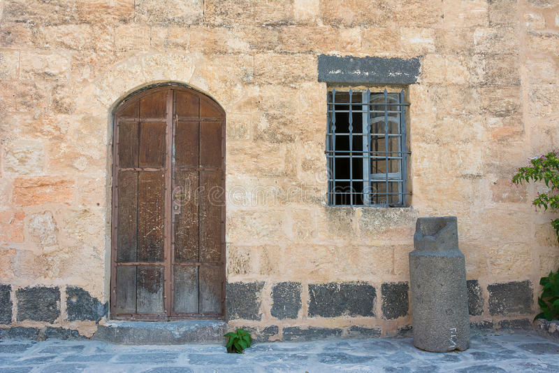 Porta di legno antica messa in parete di pietra immagini stock