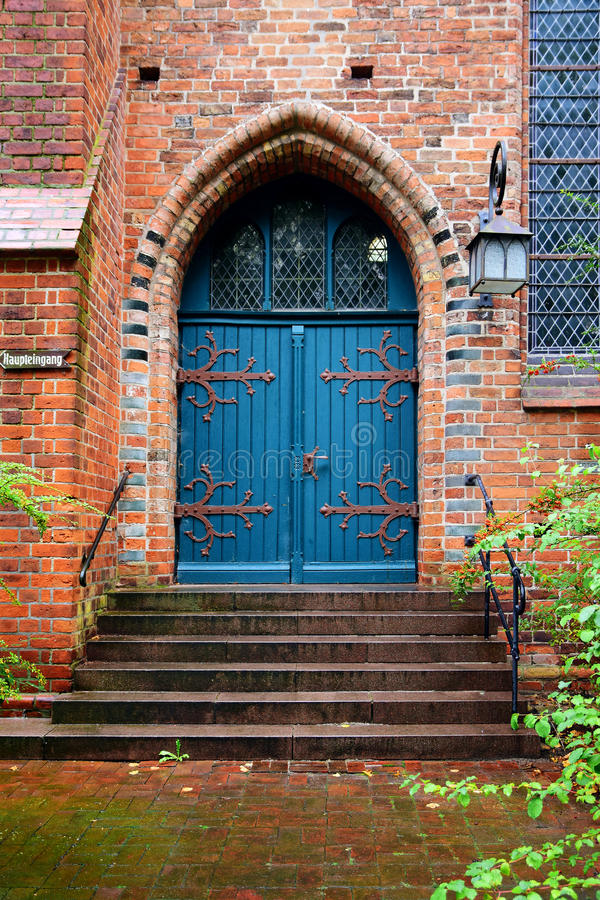 Porta di legno blu, entrata ad una vecchia chiesa del mattone fotografia stock