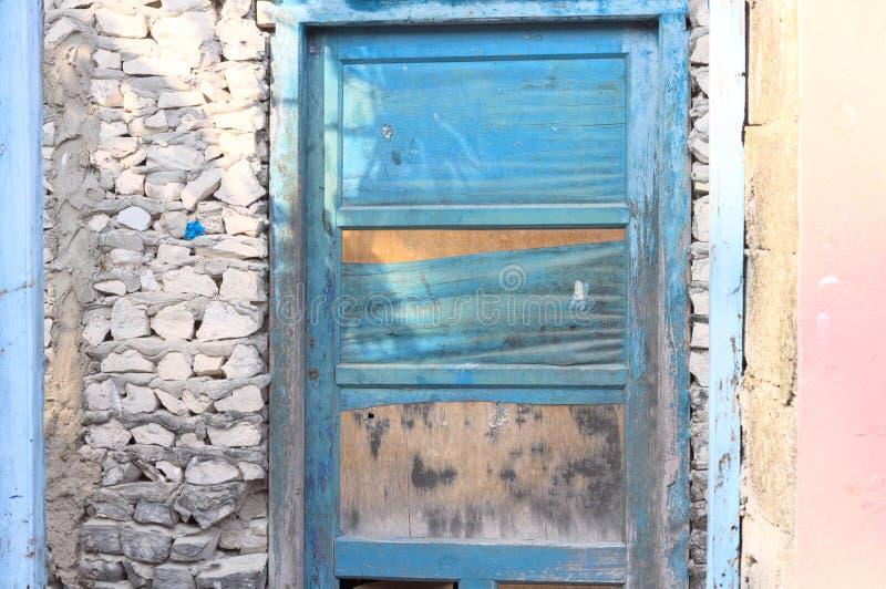 Porta di legno blu in una parete di pietra di una casa rosa abbandonata fotografie stock