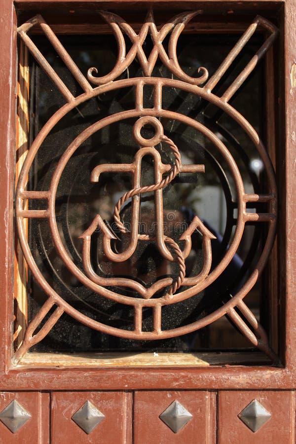 Porta di legno con il dettaglio dell'ancora in ferro battuto fotografie stock