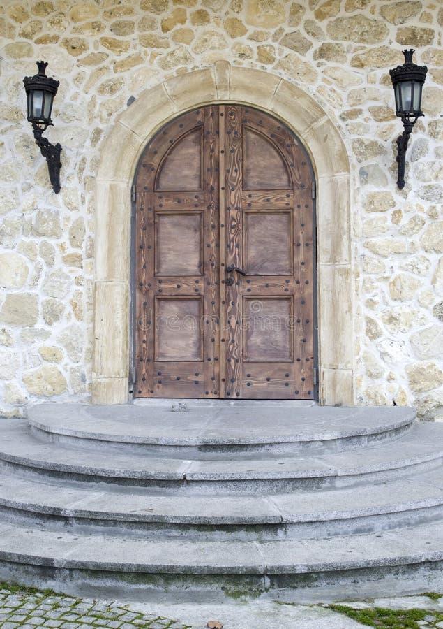 Porta di legno con l'arco sulla parete di pietra fotografie stock
