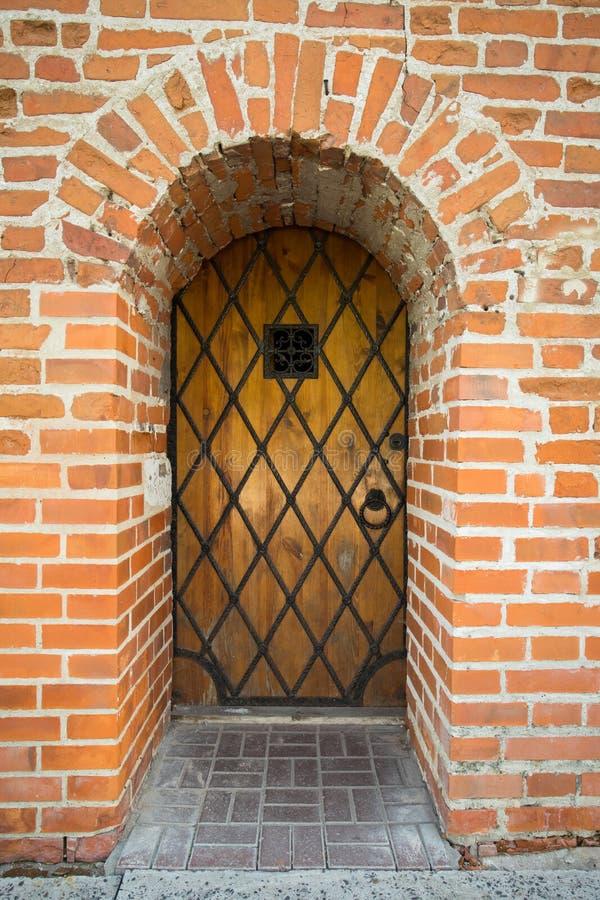 Porta di legno con la griglia del metallo e finestra in muro di mattoni immagini stock libere da diritti