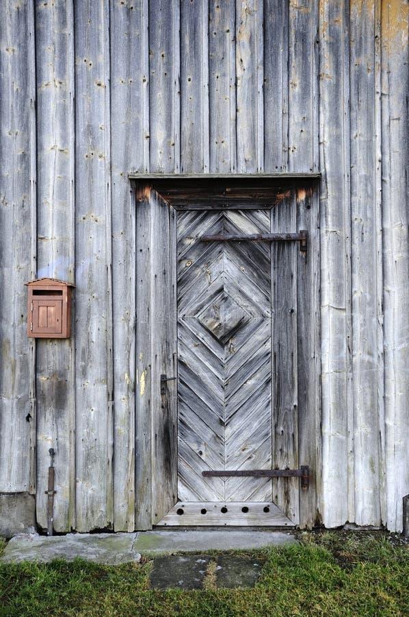Porta di legno danneggiata dalle intemperie e parete fotografia stock