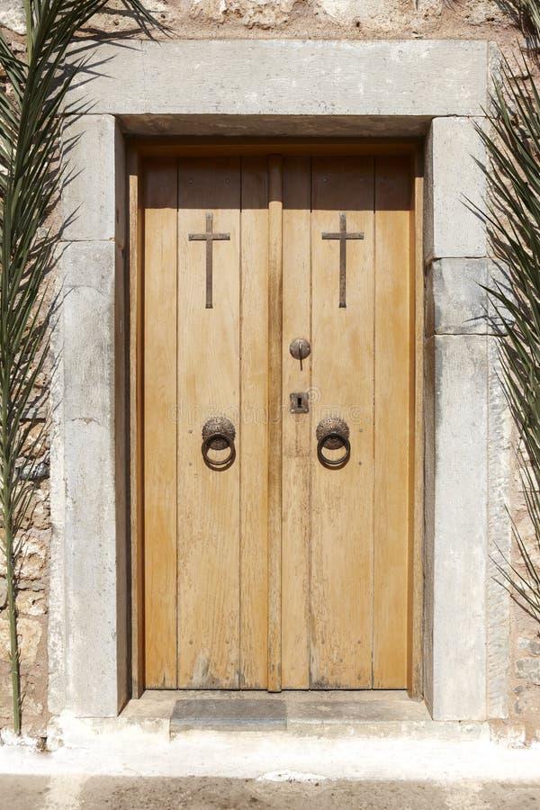 Porta di legno dell'entrata antica della chiesa con gli incroci crete La Grecia fotografia stock