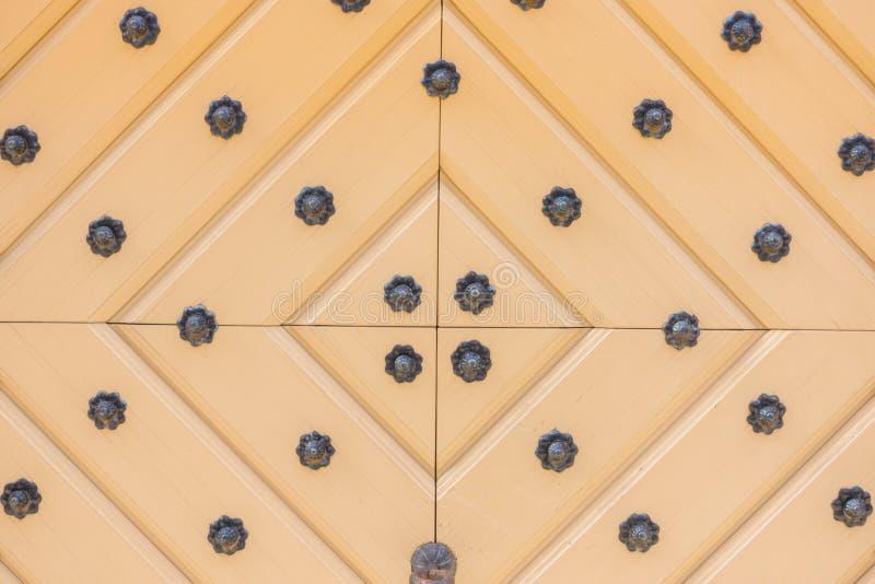 Porta di legno gialla con gli ornamenti del ferro fotografie stock libere da diritti